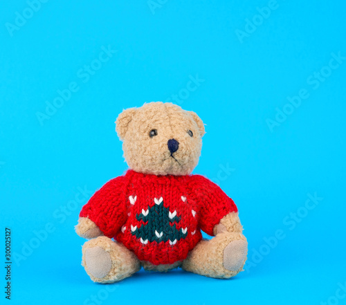 traditional toy teddy bear dressed in a red knitted sweater sits