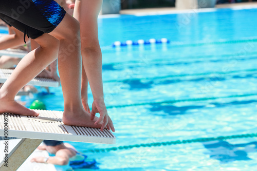 Vászonkép Cihildren on the starting blocks ready to dive into the pool at the start of a s
