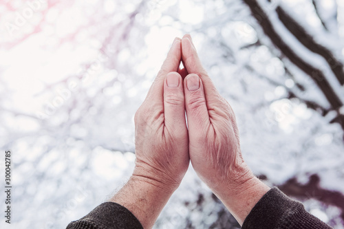 Praying hands lifted up to the sky in winter Fototapet
