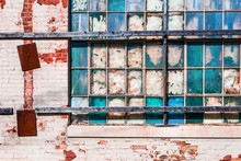 Old Industrial Windows Broken And Stuffed With Fiberglass Insulation