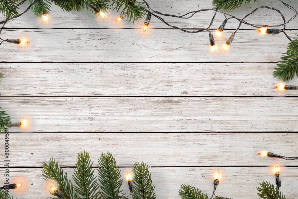 Fototapety, obrazy: Christmas lights bulb and pine leaves decoration on white wood plank, frame border design. Merry Christmas and New Year holiday background. top view.