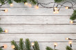 Leinwanddruck Bild - Christmas lights bulb and pine leaves decoration on white wood plank, frame border design. Merry Christmas and New Year holiday background. top view.