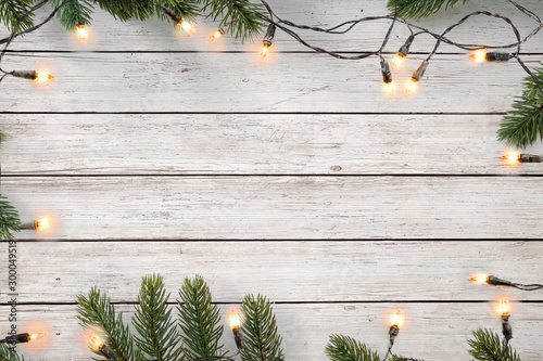 Obraz Christmas lights bulb and pine leaves decoration on white wood plank, frame border design. Merry Christmas and New Year holiday background. top view. - fototapety do salonu