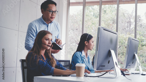 Fotografía  Customer support agent or call center with headset works on desktop computer while supporting the customer on phone call
