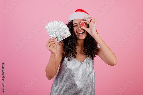 black woman with casino poker chip and cash money wearing holiday santa hat over pink - 300057719
