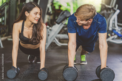 Fotografia  Couple young diversity working out in gym fitness sport complex, workout working out arms and cardio, posture position, Push up on weights,Doing plank on kettlebell