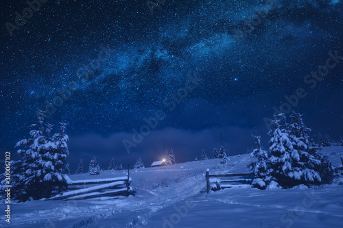 Obraz Lonely house on a snowy hill with Christmas light - fototapety do salonu