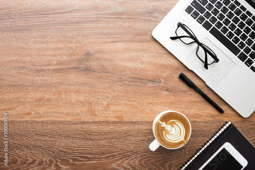 Obraz na plátně  Wood office desk table with laptop computer, cup of latte coffe, smartphone and notebook with pen