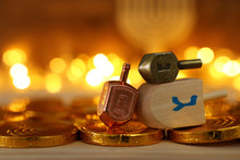 Religion Concept Of Of Jewish Holiday Hanukkah With Wooden Dreidels (spinning Top) And Chocolate Coins Over Wooden Table And Bokeh Lights Background