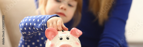 Leinwand Poster Child little girl arm putting coins into piggybank