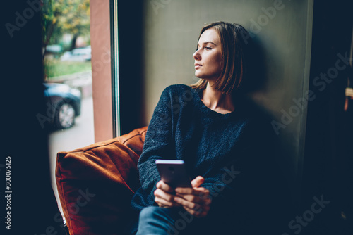 Fotografiet Thoughtful young woman dressed in black casual outfit looking out of window resting in comfortable coworking space