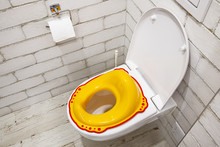 Yellow Lid For Toilet Seat For Children. How To Accustom A Child To The Toilet. White Bathroom.