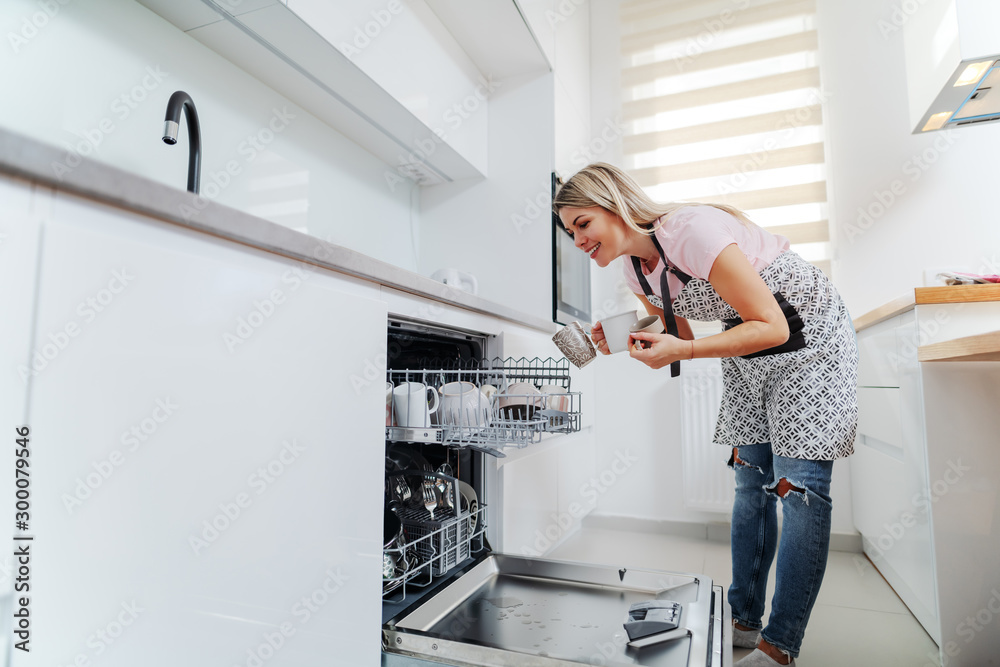 Fototapeta Worthy caucasian housewife in apron putting mugs in dishwasher while standing in kitchen.