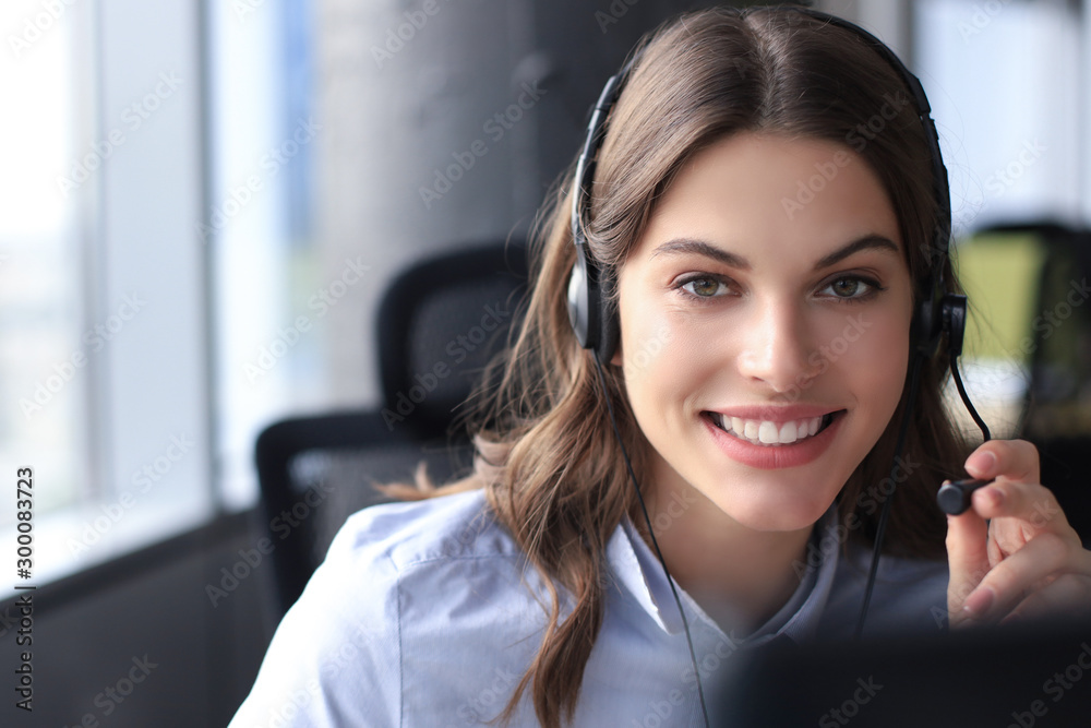 Fototapeta Female customer support operator with headset and smiling.