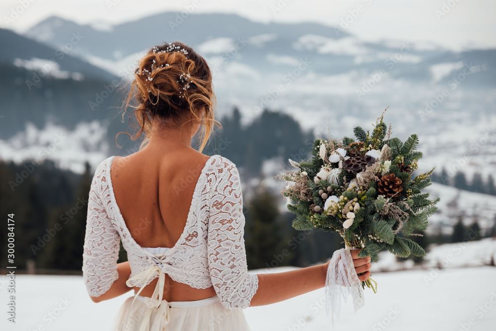Fototapety, obrazy: Bride in white wedding dress holding colorful flowers bouquet in hands and posing outdoors. Winter wedding and season floral concept. Mountains on background.