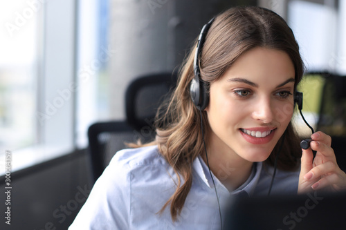 Beautiful smiling call center worker in headphones is working at modern office Billede på lærred