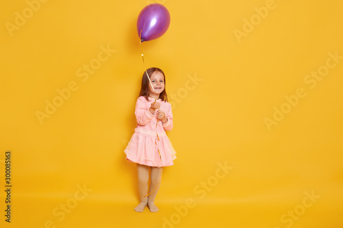 Obraz Studio shot of little girl wearing rose dress playing with purple balloon isolated over yellow background, having birthday, having fun with balloon, cute female child with dark hair. Childhood concept - fototapety do salonu