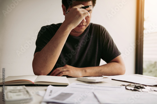 Fotomural Asian men are stressed about financial problems, with invoices and calculators placed on the table while having stress on problems with home expenses