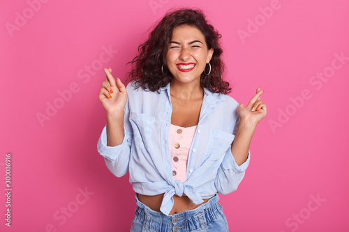 Horizontal shot of young attractive female keeps her fingers crossed and eyes closed, looks wishful and thinking, studio shoot isolated over pink background, girl wearing blue shirt and jeans. - 300086916
