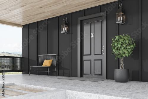 Photo Black door of black house, tree and bench