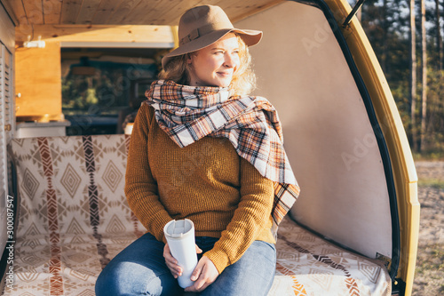 Young blonde Caucasian woman relaxing in her campervan at sunset Fototapet