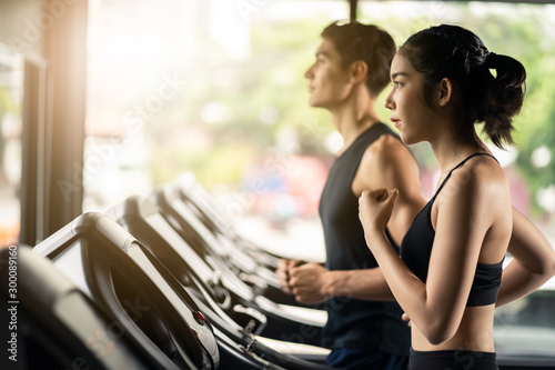 Young fit two friends of Caucasian man and Asian woman exercising and working out in gym Tablou Canvas