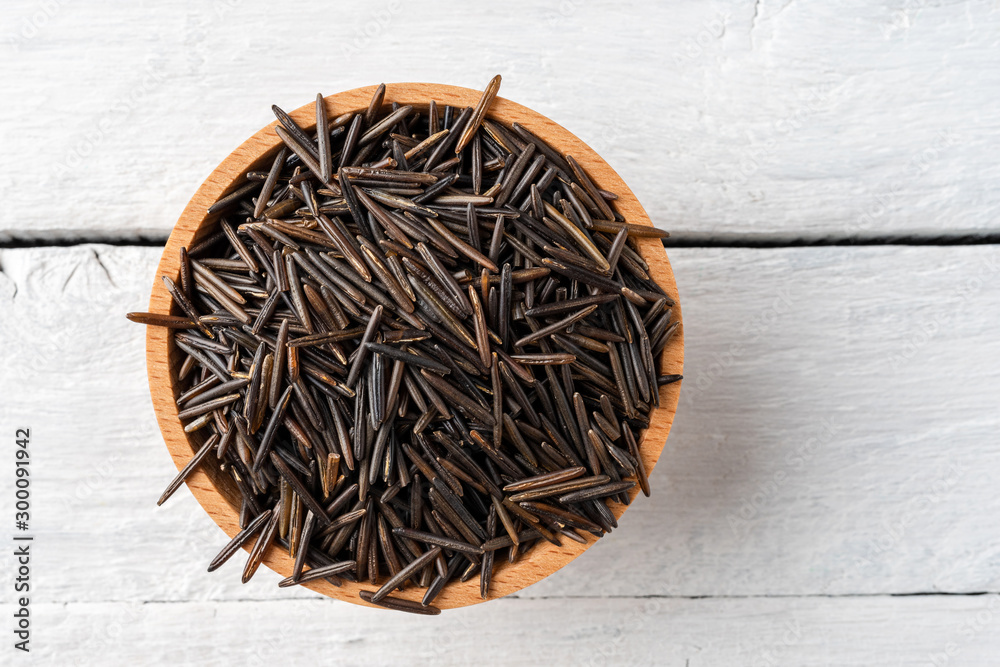 Fototapeta Wild rice in bowl on rustic wooden table. Top view