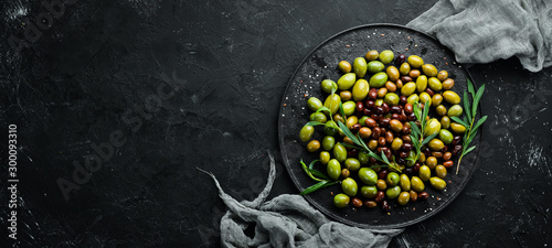 Fototapeta Olives in a bowl, olive oil, spices and herbs. Top view. Free space for your text. obraz