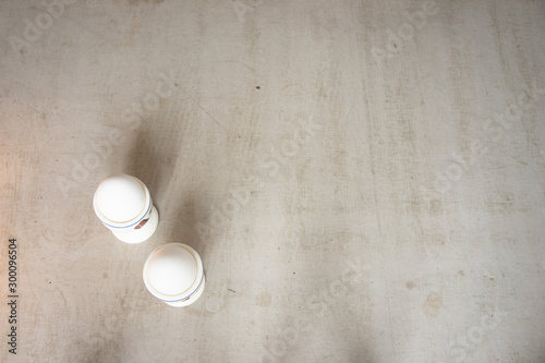 Fotobehang Macarons two eggs in cups standing on concrete table