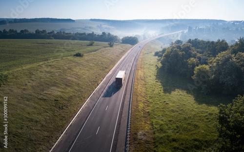 fototapeta na szkło Aerial Top View of White Truck with Cargo Semi Trailer Moving on Road in Direction