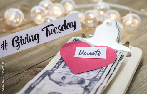 Fotografía  Giving Tuesday donate charity concept with text and cash on wooden board