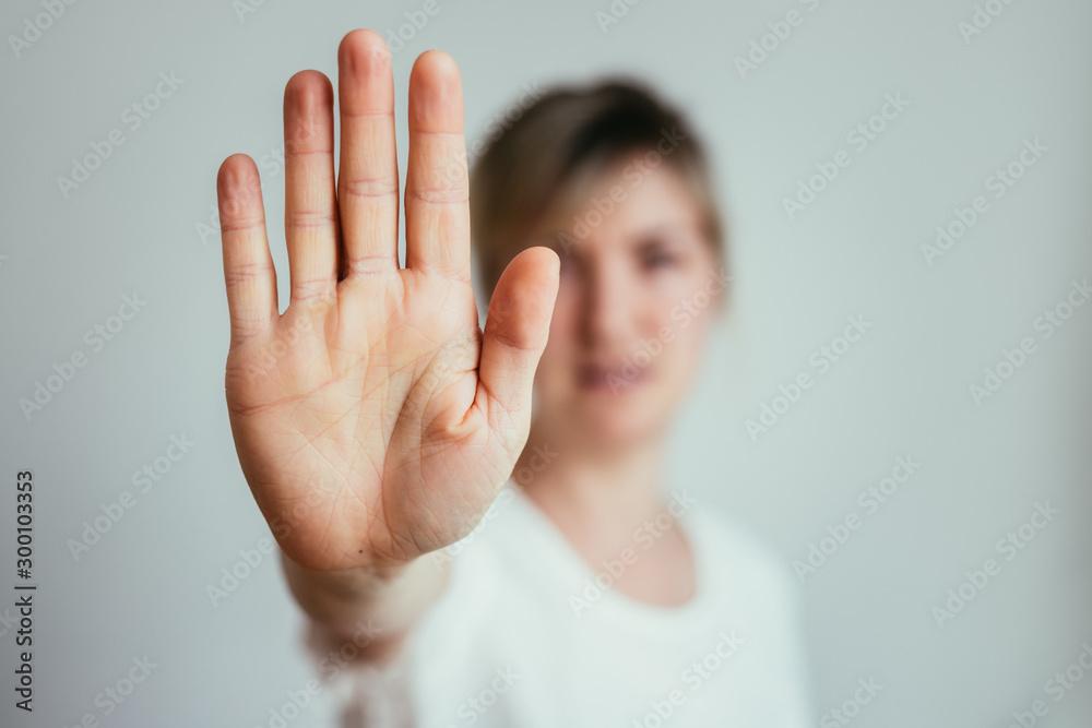 Fototapeta Defense or stop gesture: Girl hand with stop gesture