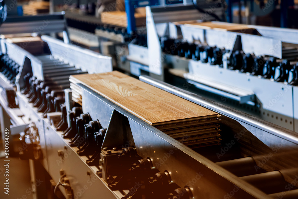 Fototapeta Production line of the wooden floor factory. CNC automatic woodworking machine.