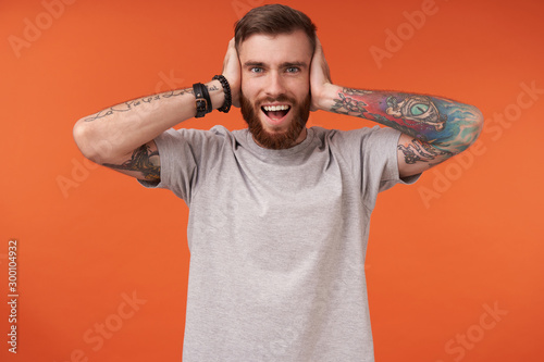 Fotografija  Happy bearded brunette man with tattooes covering his ears with raised palms and