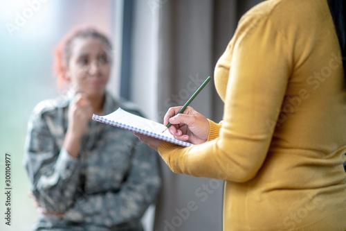 Valokuva  Female psychoanalyst wearing yellow sweater making notes