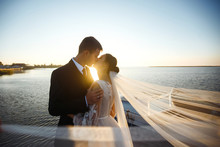 Pretty Bride And Stylish Groom Together On The Bridge Against The Background Of The Boat. Newlyweds Enjoy Each Other Tenderly In The Shadow Of A Flying Veil. Together. Wedding. Love.