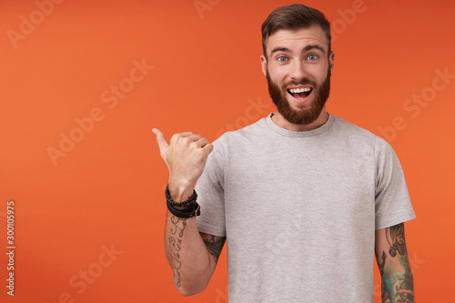 Happy pretty bearded tattooed man with trendy haircut looking at camera with wid Slika na platnu