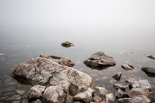 Stones On The Lake In The Fog. Big And Small Stones. The Water Is Transparent And Under The Water You Can See Stones Overgrown With Silt. Copy Space.