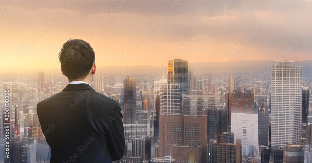Fototapeta Businessman looking at futuristic city in sunset. Business concept