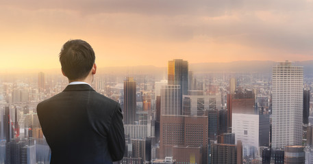Fototapeta na wymiar Businessman looking at futuristic city in sunset. Business concept