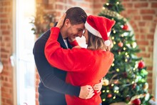 Young Beautiful Couple Smiling Happy And Confident. Standing And Hugging Around Christmas Tree At Home