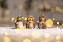 Set Of Decorative Figurines Toy Owl With A Golden Crown On His Head. Festive Decor, Warm Bokeh Lights