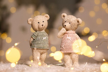 Decorative Figurines Of A Christmas Theme. Figurines Of Cute Teddy Bears Of A Boy And A Girl In Sweaters With Deers. Festive Decor, Warm Bokeh Lights.