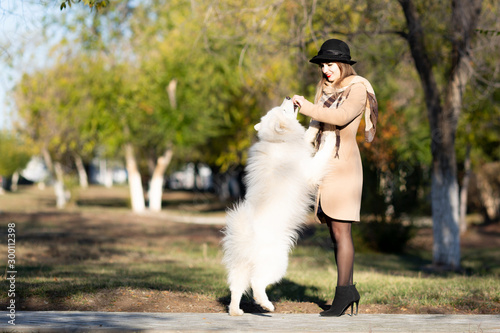 Photo  A young woman is playing with her dog in a park