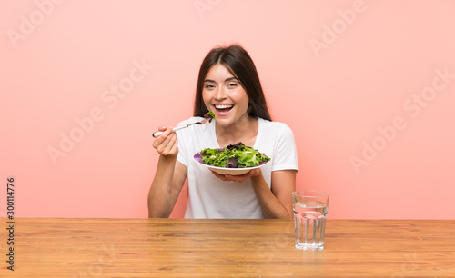 Fotografía  Young woman with a salad in a table