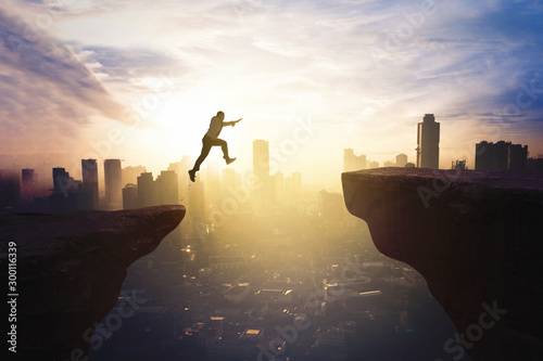 Businessman jumping through gap cliff at sunrise Fotobehang