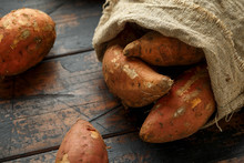 Raw Sweet Potatoes On Rustic Wooden Table