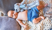 Adorable Baby Lying Down On The Sofa Over Blanket At Home. Newborn Relaxing And Resting Comfortable With Doll