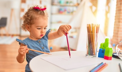 Beautiful caucasian infant playing with toys at colorful playroom. Happy and playful drawing with color pencils at kindergarten.