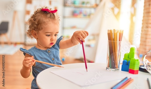 Obraz Beautiful caucasian infant playing with toys at colorful playroom. Happy and playful drawing with color pencils at kindergarten. - fototapety do salonu